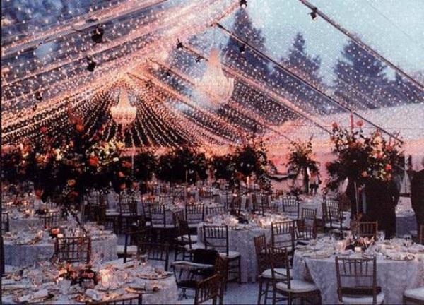 carpa transparente decorada con luces de navidad y candelabros